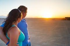 Couples dans l'étreinte observant ensemble le coucher du soleil Images libres de droits