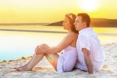 Couples dans l'étreinte observant ensemble le lever de soleil Images libres de droits