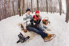 Couples dans l'amour étreignant en parc d'hiver et se reposant sur la couverture Photographie stock