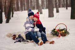 Couples dans l'amour étreignant en parc d'hiver et se reposant sur la couverture Photo libre de droits