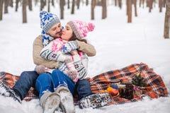 Couples dans l'amour étreignant en parc d'hiver et se reposant sur la couverture Images libres de droits