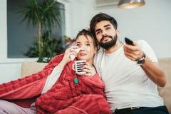 Couples dans l'amour étreignant et appréciant l'exposition de TV Photos stock