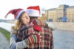 Couples dans l'amour étreignant les chapeaux dehors de port de Noël Photos libres de droits