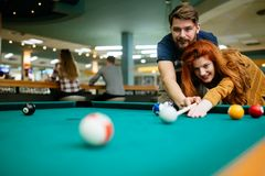 Couples dans l'amour appréciant jouant le billard dans la barre Photographie stock libre de droits