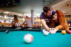 Couples dans l'amour appréciant jouant le billard dans la barre Images libres de droits