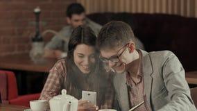 Couples dans l'amour appréciant le temps dans un club de narguilé et prenant le selfie Photo libre de droits