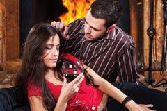 Couples dans l'amour appréciant le vin près de la cheminée Images libres de droits