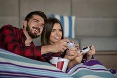 Couples dans l'amour appréciant leur temps gratuit, se reposant sur un divan à côté de la fenêtre, jouant des jeux vidéo et ayant photos libres de droits