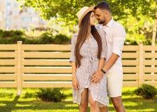 Couples dans l'amour au coucher du soleil marchant en parc heureux, dre américain Image libre de droits