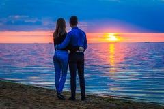 Couples dans l'amour au coucher du soleil par la mer image libre de droits