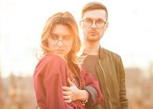 Couples dans l'amour au coucher du soleil posant in camera Photographie stock libre de droits