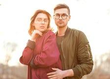 Couples dans l'amour au coucher du soleil posant in camera Image libre de droits