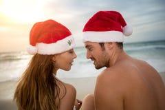 Couples dans l'amour avec des chapeaux de Santa sur la plage Images libres de droits