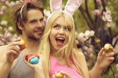 Couples dans l'amour avec des oreilles de lapin tenant les oeufs color?s image libre de droits