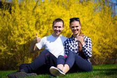 Couples dans l'amour avec des pouces se reposant en parc sur l'herbe verte fraîche Images libres de droits
