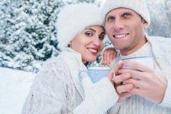 Couples dans l'amour avec des tasses de thé chaud dans la forêt d'hiver de neige Photos stock