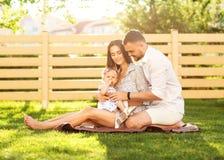Couples dans l'amour avec la petite fille sur un pique-nique près de leur maison, Photographie stock