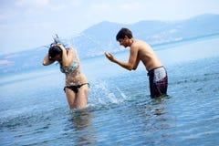 Couples dans l'amour ayant l'amusement avec de l'eau dans les vacances Photos libres de droits