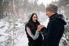 Couples dans l'amour buvant du thé chaud dans la forêt neigeuse Photo libre de droits