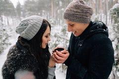 Couples dans l'amour buvant du thé chaud dans le jour d'hiver froid neigeux Image libre de droits