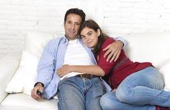 Couples dans l'amour caressant sur le film de observation de détente de divan à la maison à la télévision avec l'homme jugeant à  Image stock