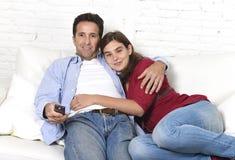 Couples dans l'amour caressant sur le film de observation de détente de divan à la maison à la télévision avec l'homme jugeant à  Photos stock