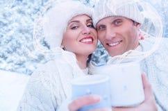 Couples dans l'amour dans la forêt de neige avec le cadre de coeur de la vapeur Photographie stock