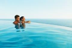 Couples dans l'amour dans la piscine de lieu de villégiature luxueux des vacances d'été romantiques Images stock