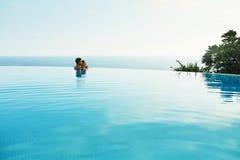 Couples dans l'amour dans la piscine de lieu de villégiature luxueux des vacances d'été romantiques Photographie stock