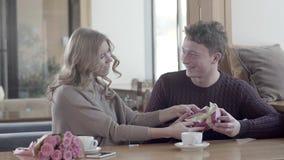Couples dans l'amour dans un café : un homme donnent des cadeaux le jour du ` s de Valentine banque de vidéos