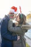 Couples dans l'amour dehors avec des chapeaux de Noël Image libre de droits