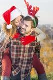 Couples dans l'amour dehors avec des chapeaux de Noël Photo stock