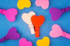 Couples dans l'amour des coeurs en bois entourés par les coeurs colorés dessus Photographie stock