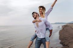 Couples dans l'amour des vacances d'été de plage Fille joyeuse ferroutant sur le jeune ami ayant l'amusement photo stock