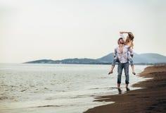 Couples dans l'amour des vacances d'été de plage Fille joyeuse ferroutant sur le jeune ami ayant l'amusement photographie stock