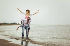 Couples dans l'amour des vacances d'été de plage Fille joyeuse ferroutant sur le jeune ami ayant l'amusement images stock