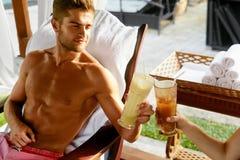 Couples dans l'amour des vacances romantiques avec des cocktails à la station thermale Photos libres de droits