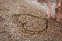 Couples dans l'amour dessinant un coeur sur le sable Images libres de droits
