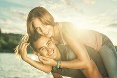 Couples dans l'amour embrassant au lac, fusée du soleil Photos stock