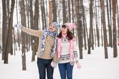 Couples dans l'amour embrassant dans la forêt dans des chandails d'hiver Le type indique avec la main Image libre de droits