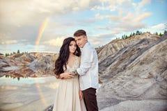 Couples dans l'amour embrassant et étreignant sur le fond de l'arc-en-ciel et des montagnes Un homme et un amour de femme fabuleu Images libres de droits