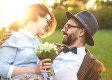 Couples dans l'amour en nature étreignant avec des fleurs sur le ` s de St Valentine Photos stock