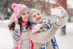 Couples dans l'amour faisant le selfie l'hiver dehors dans les chandails, l'écharpe et des mitaines Photo libre de droits