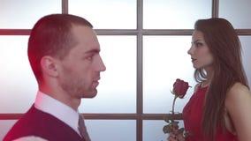 Couples dans l'amour Femme de brune avec une rose dans des ses mains banque de vidéos