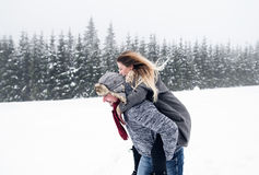 Couples dans l'amour, homme donnant le ferroutage de femme Nature de l'hiver Photos stock