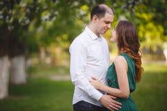 Couples dans l'amour : jeune fille et homme presque chauve dans le jardin Image stock