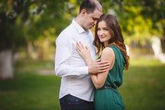 Couples dans l'amour : jeune fille et homme presque chauve dans le jardin Photographie stock libre de droits
