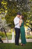 Couples dans l'amour : jeune fille et homme presque chauve dans le jardin Photos libres de droits