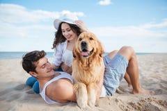 Couples dans l'amour jouant avec leur chien sur la plage Photographie stock