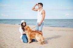Couples dans l'amour jouant avec leur chien sur la plage Photo stock